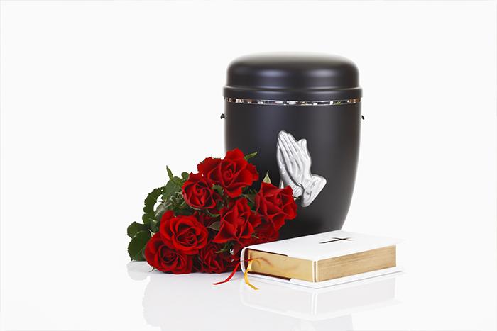 urne funeraire noire avec bouqet de fleurs rouges à côté d'une bible